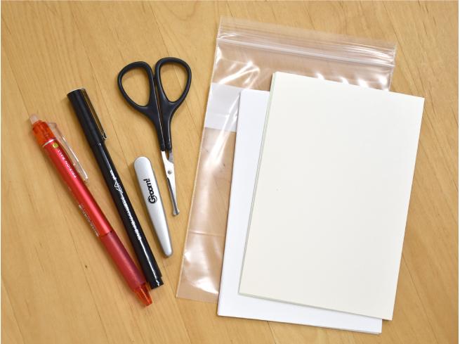 僕の基本の秘密道具。左から、赤の消せるボールペン、黒の水性ペン、鼻毛切り用ハサミ(ハサミの横にあるのはケースです)、ジッパー付きビニール袋A6サイズ、A4コピー用紙を4等分したもの、ハガキサイズのケント紙(年賀状などの試し刷り用紙)。紙の切りくずや、できた作品はビニール袋に入れて持ち帰ります。