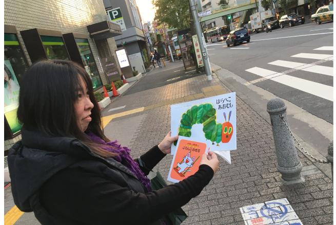 ちょっとはにかむ坂川由美香さんの画像。手には『はらぺこあおむし』と『ノンタンぶらんこのせて』