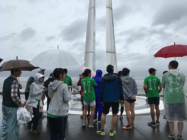 雨の中、コース説明をうける選手たち。傘をさしている。遠くに諏訪湖が見える。