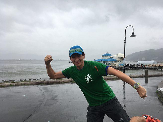 琵琶湖のまえで走るポーズをしておどける著者。