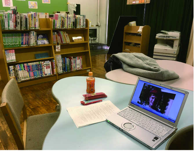 図書室のいすと机の写真。机にはパソコンと原稿、ペットボトル、筆記具が置かれている。
