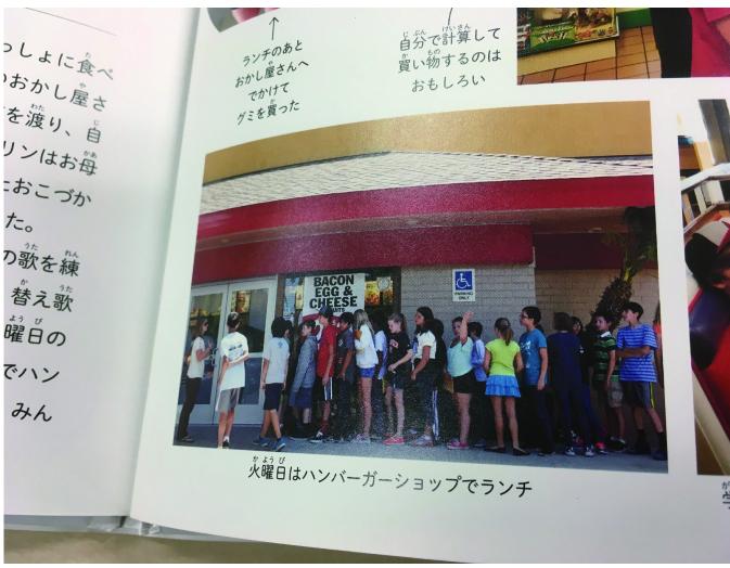 本を開いたところの写真。子どもたちがファストフード店に行列する写真が載っている。