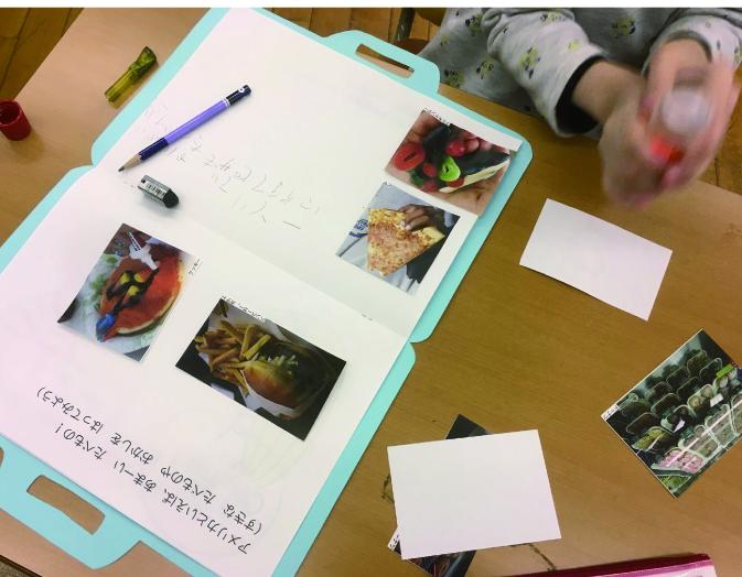 かばんの形をした制作物をひらいている写真。一緒に子どもの手が写っている。