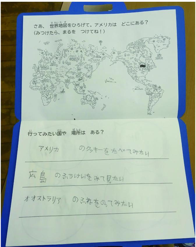 かばんの形をした制作物を開いている写真。世界地図の絵があり、行ってみたい国を子どもが書いている。アメリカ、広島、オーストラリアに行きたいと書かれている。