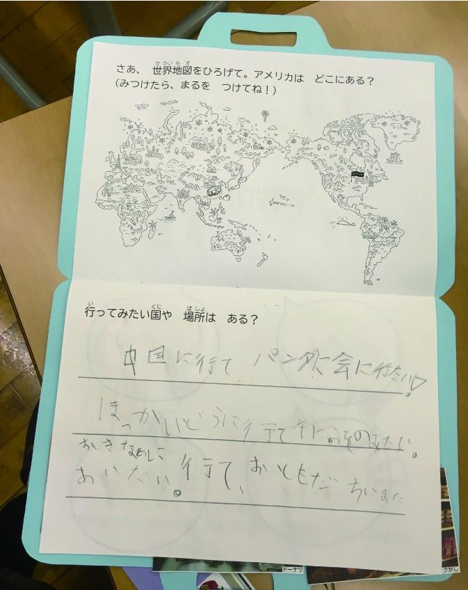 かばんの形をした制作物を開いている写真。世界地図の絵があり、行ってみたい国を子どもが書いている。中国。北海道。沖縄。