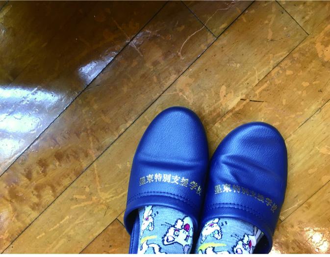 ノンタンの靴下と「墨東特別支援学校」と書かれたスリッパの写真。