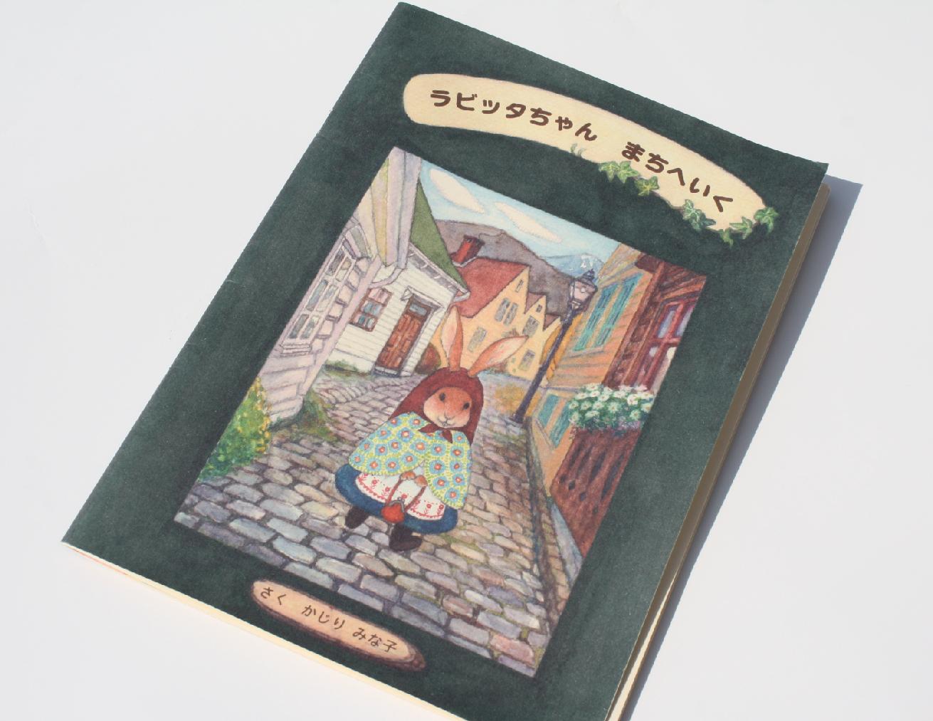 私家版絵本「ラビッタちゃんまちへいく」の表紙。レンガの道をラビッタちゃんが歩いている。