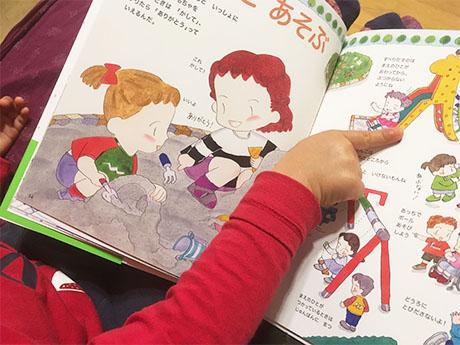 本を開いて、絵を指差す子どもの写真