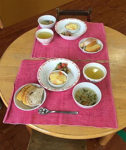 パンやスープ、グラタンなどがならんだテーブルの写真