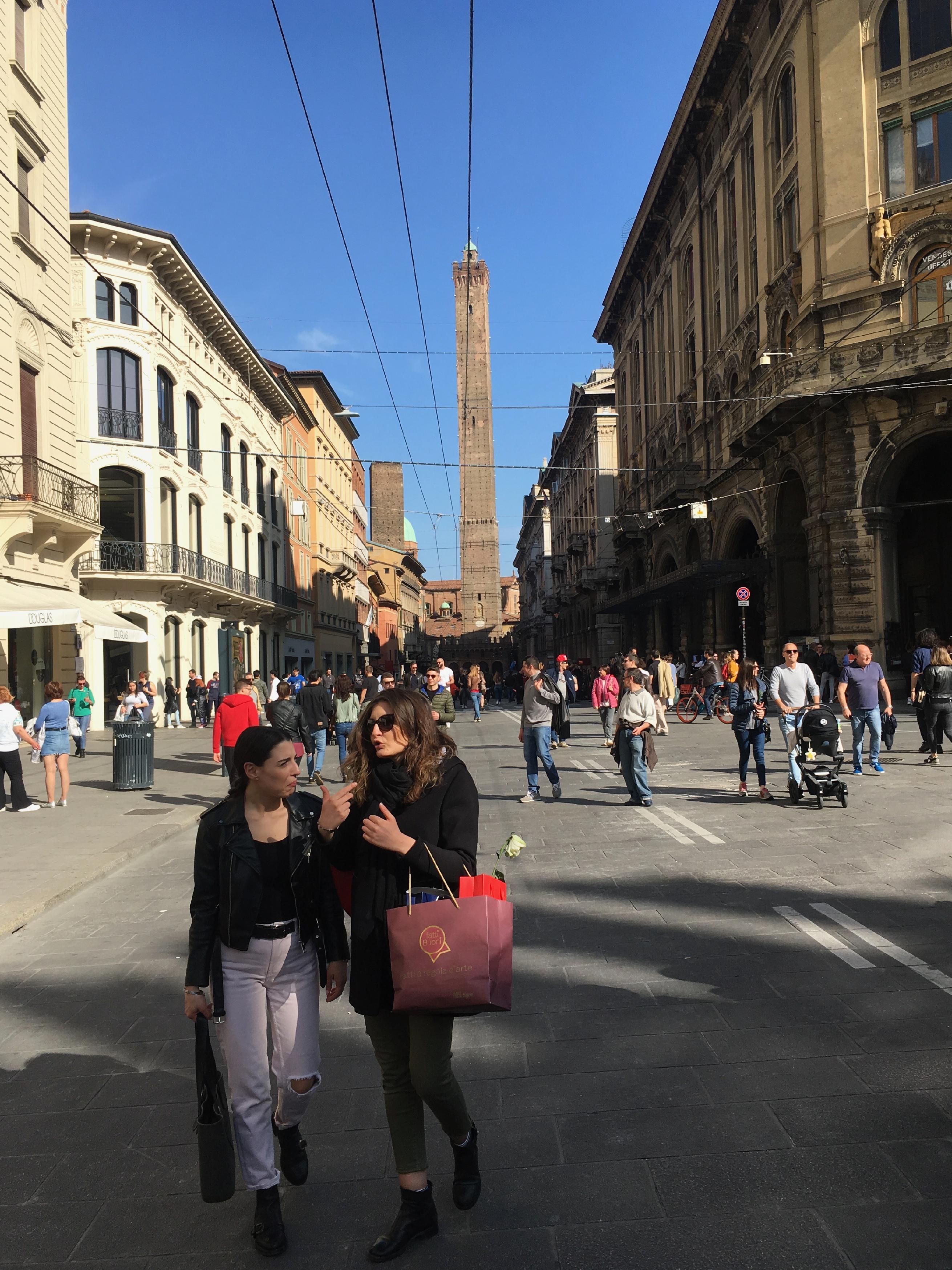 ボローニャの街並み。奥に高く細長い塔がみえる。手前におしゃれな女性2人組