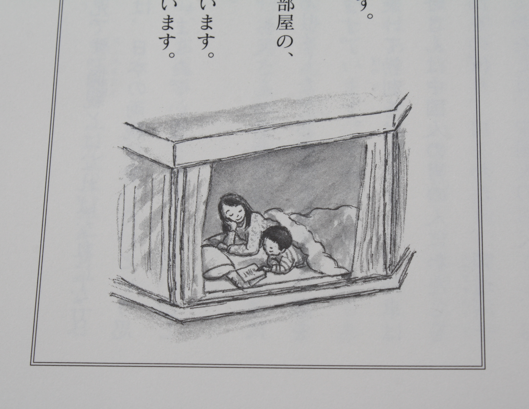 さし絵。母親が布団のうえのむすこになにか読み聞かせている様子。
